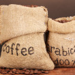 Coffee beans in bags on table on dark background — Stock Photo
