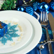 Small Christmas gift on plate on serving Christmas table in blue toneclose-up — Stock Photo