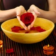 Stock Photo: Womhands with wooden bowl of water with petals