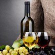 Bottles and glasses of wine and grapes on grey background — Stock Photo #15737875