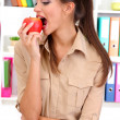 Young businesswoman eating an apple — Stock Photo #15738173