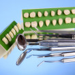 Set of dental tools with denture on blue background - Stock Photo