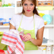 A young girl dries dishes in kitchen - Stock Photo
