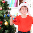 Little boy in Santa hat decorates Christmas tree in room — Stock Photo #15739097