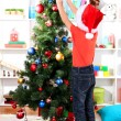 Little boy in Santa hat decorates Christmas tree in room — Stock Photo #15739103