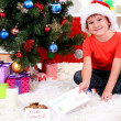 Little boy in Santa hat with milk, cookies and letter for Santa Claus — Stock Photo #15739109