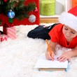 Little boy in Santa hat writes letter to Santa Claus - Стоковая фотография