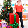Child in Santa hat near Christmas tree with big gift - Стоковая фотография