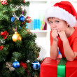 Child in Santa hat near Christmas tree with big gift — Stock Photo #15739127