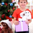 Little boy sits near Christmas tree with gift in hands — Stock Photo #15739149