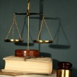 Golden scales of justice, gavel and books on grey background — Stock Photo #15739191