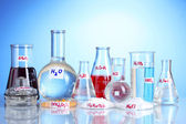 Test-tubes with various acids and chemicals on blue background — Stock Photo