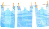Cellophane bags hanging on rope isolated on white — Stock Photo
