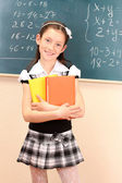 Beautiful little girl in school uniform with books in class room — Stock Photo