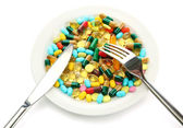 Colorful capsules and pills on plate with fork and knife, isolated on white — Stock Photo