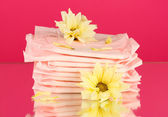 Panty liners in individual packing and yellow flower on pink background close-up — Stock Photo