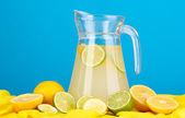 Citrusovou limonádu v sklenice džbán citrusů kolem na žlutou látku na modrém pozadí — Stock fotografie