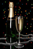 Celebratory champagne with wineglass on Christmas lights background — ストック写真