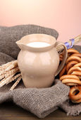 Jar of milk, tasty bagels and spikelets on wooden table, on brown background — Stock Photo