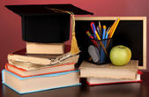 Books and magister cap against school board on wooden table on red background — Stock Photo