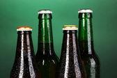 Bottiglie di birra di vetro colorate su sfondo verde — Foto Stock