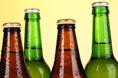 Coloured glass beer bottles on yellow background — Stock Photo