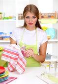 Una joven seca platos en la cocina — Foto de Stock