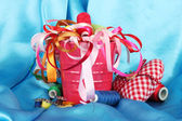Color bucket with multicolor ribbons and thread on blue fabric background — Stock Photo