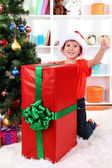 Child in Santa hat near Christmas tree with big gift — Stock Photo