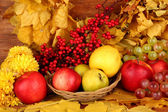 Autumnal composition with yellow leaves, apples and mushrooms on wooden background — Stock Photo