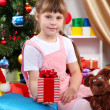 Little girl sits near a Christmas tree with gift in hand in festively decorated room — Stock Photo #15747109