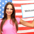 Young woman young woman holding tablet on background of American flag — Stock Photo #15740459