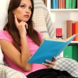 Portrait of female reading book at home — Stock Photo