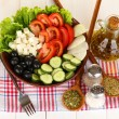 Tasty Greek salad with spices on white wooden background close-up - Stock Photo