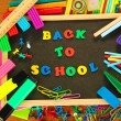 Stock Photo: Small chalkboard with school supplies on wooden background. Back to School