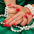 Female hands holding beads on color background — Stockfoto