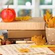 Autumnal composition with gift, books and leaves on bright background — Stock Photo