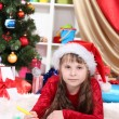Beautiful little girl writes letter to Santa Claus in festively decorated room — Stock Photo #15747133