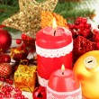Red candle with christmas decoration on light background — Stock fotografie