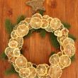Christmas wreath of dried lemons with fir tree and star, on wooden background — ストック写真