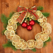Christmas wreath of dried lemons with fir tree and balls, on wooden background — Zdjęcie stockowe
