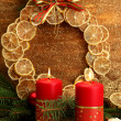 Two candles and christmas decorations, on golden background — Stock Photo #15747409