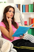 Portrait of female reading book at home — Stockfoto