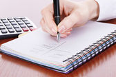 Women hands with pencil, notebook and Calculator on wooden table — Stock Photo