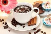 Tasse de café et gerbera, haricots, bâtons de cannelle sur table en bois — Photo