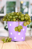 Ripe green grapes in pail on wooden table on window background — Stock Photo