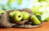 成熟的绿色苹果上麻布,木桌上,在绿色背景上的篮子里 — 图库照片