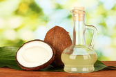 Decanter with coconut oil and coconuts on green background — Photo