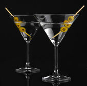Martini glasses and olives isolated on black — Stock Photo