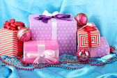 Colorful gifts with pink Christmas balls, snowflakes and beads on blue background — Stock Photo